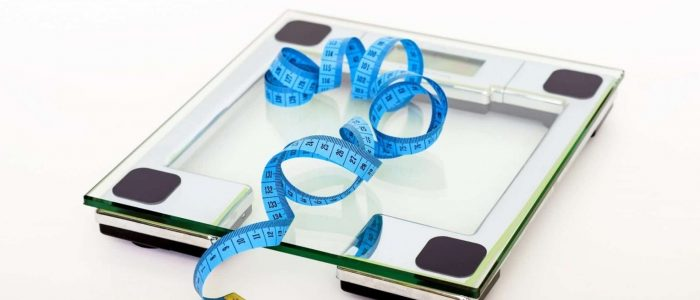 blue-tape-measuring-on-clear-glass-square-weighing-scale-53404